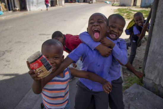 Vier Kinder posieren lachend vor der Kamera