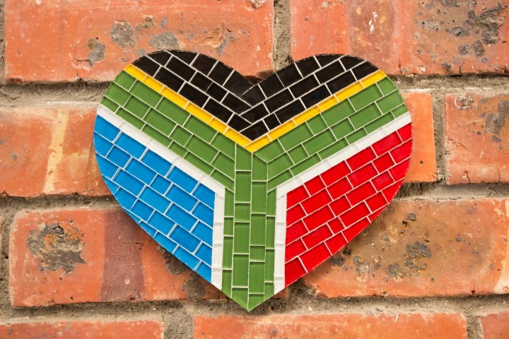 Ein Herz aus buntem Mosaik formt die Flagge Südafrikas auf rotem Backstein