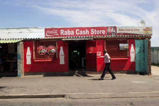 Ein Mann läuft an einem roten Shop vorbei - Townshiptour in Kapstadt