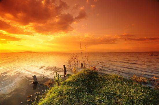 über einem See geht die Sonne im orangen Himmel unter