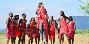 Touriste sautant au milieu d'un groupe de Maasaï