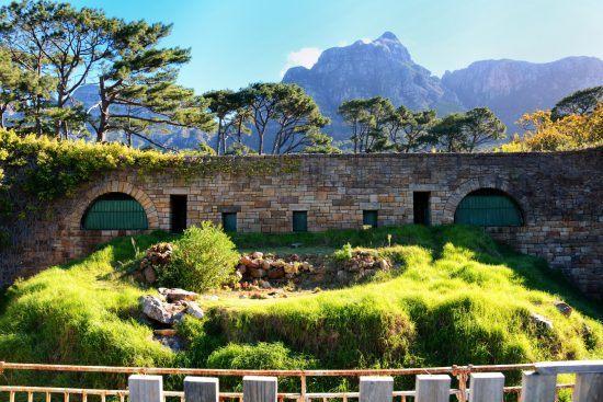 Ein alter Löwenkäfig, dahinter die Bergkette in Kapstadt