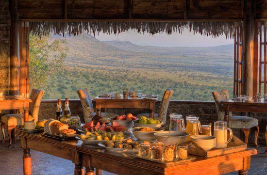 Im Vordergrund ein Frühstücksbuffet, dahinter ein Tisch mit Ausblick auf die Savanne