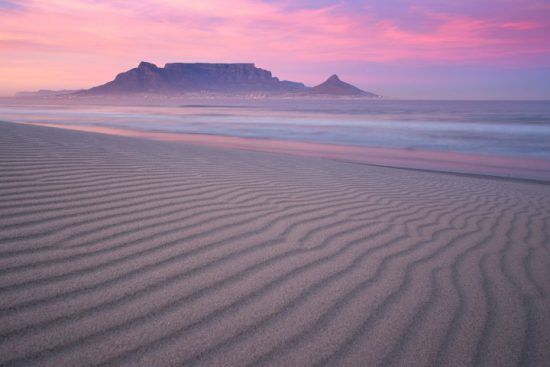 The silhouette of Table Mountain in front of a pink-purple sky