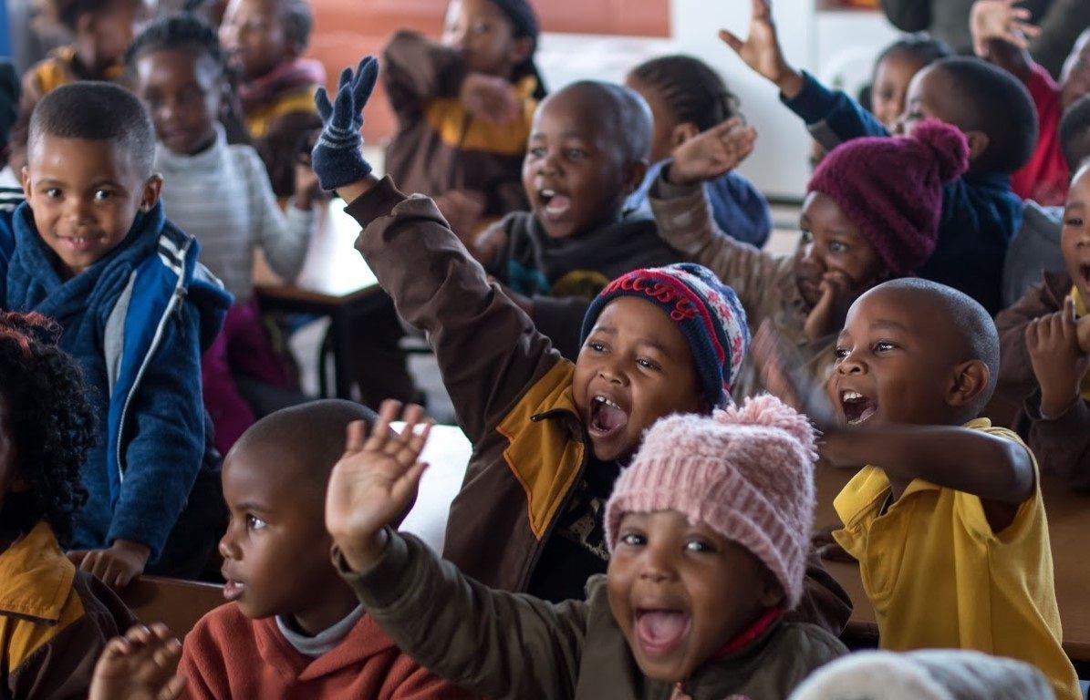 Kinder sitzen bei einer Versammlung zusammen und strecken ihre Arme in die Luft