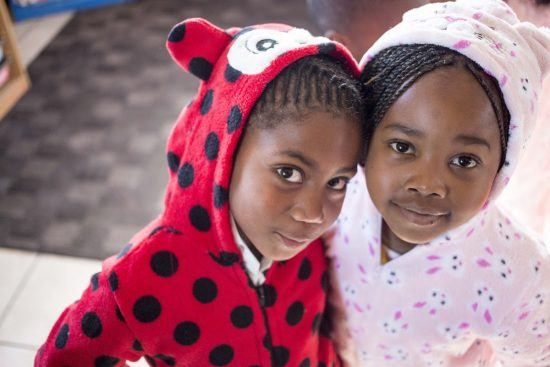Two girls dressed up in onesies at Khumbulani