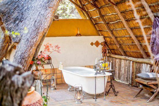 Eine freistehende Badewanne unter einem reetgedeckten Dach