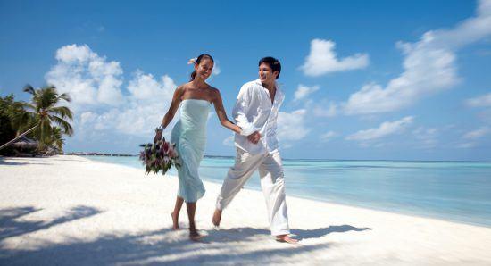 Casal caminha pela praia na ilha de Kuda Huraa, durante estadia no Four Seasons Resort, em Maldivas