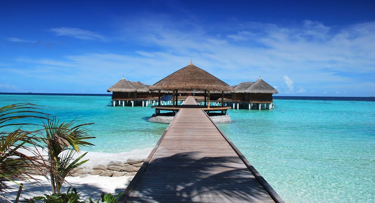 Passarela de madeira leva a cabanas elevadas sobre o Oceano Índico em Maldivas