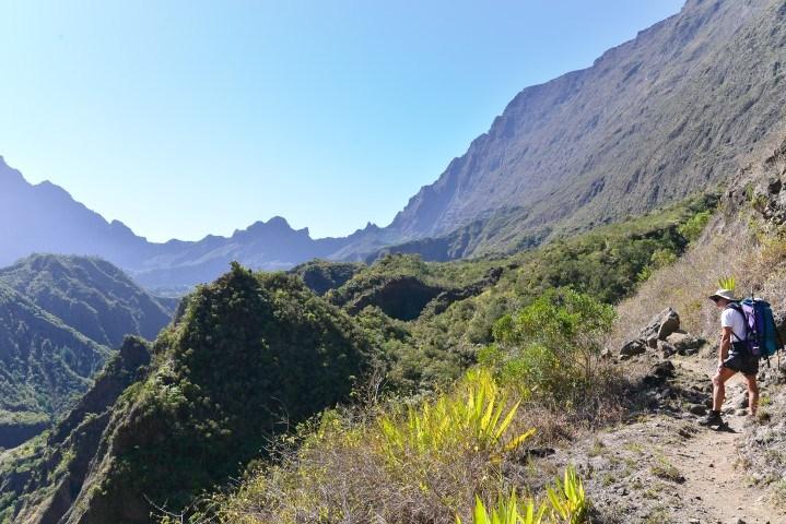 Eine Frau wandert durch die grünen Berge auf La Réunion - erleben Sie die Vulkane auf La Réunion