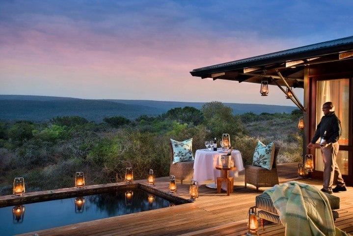 Ein gedeckter Tisch neben einem Pool in einer Suite der Kwandwe Ecca Lodge bei Sonnenuntergang