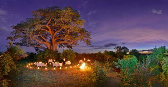 Ein romantisch beleuchteter Tisch im Busch nahe des Sambesiufers