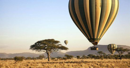 Hot air balloons floating above the savanna in Kenya