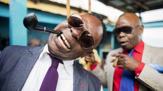 Zwei Sapeurs in schicker Kleidung, mit Sonnenbrille und Pfeife im Mund posieren für die Kamera