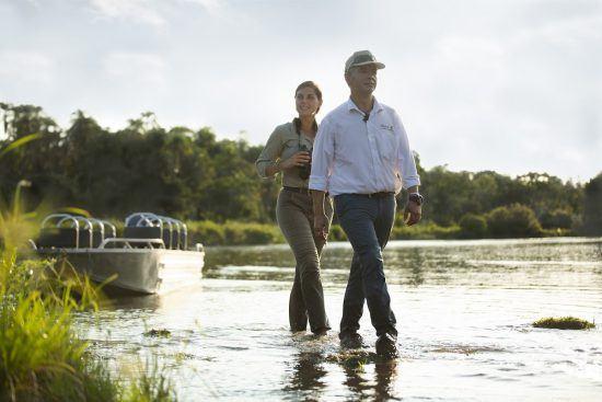 Mann und Frau schreiten nach einer Bootstour durchs Wasser