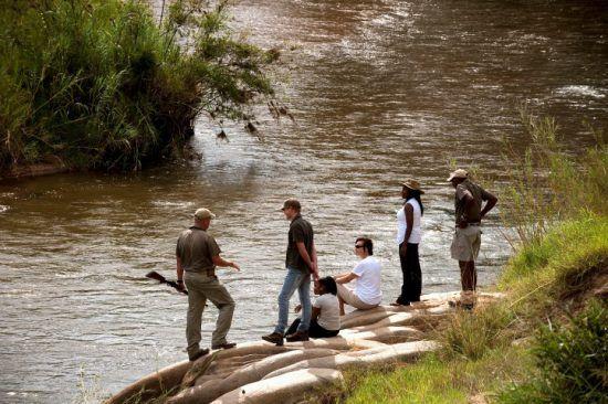 Safari-Urlauber auf einer Buschwanderung im Lion Sands Game Reserve an einem Fluss