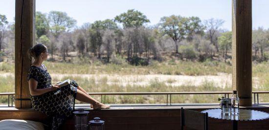 Isolation zu Hause: Frau sitzt auf einer Terrasse und liest ein Buch