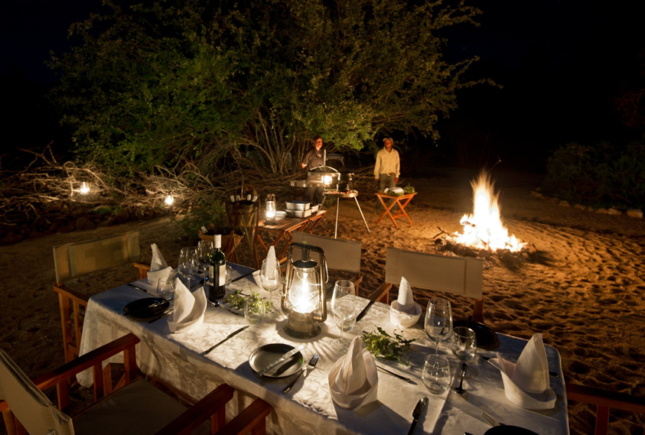 Boma dinner by glowing lamp-light and campfire-cooking